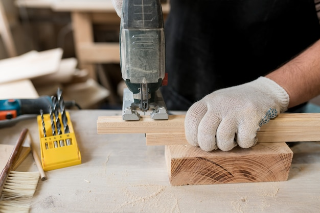 Close up of hand carpenter working on wood with electric jigsaw in workshop sawing wooden board