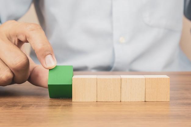 クローズアップ手は、グラフィックなしで積み重ねられた立方体の木製おもちゃのブロックを選択します。