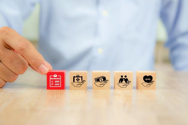 クローズアップ手は安全家族保険の概念のための家族のアイコンが付いた赤い木のおもちゃのブロックを選択します。