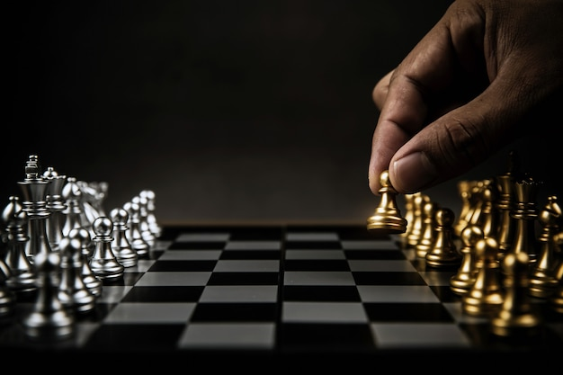 Close up hand choose chess from the golden team on chess board.