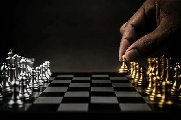 Закройте вверх руки выберите шахматы из золотой команды на шахматной доске.