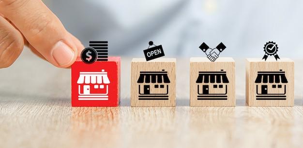 클로즈업 손으로 프랜차이즈 비즈니스 스토어 아이콘에 맞춰 큐브 나무 장난감 블록 장소를 선택합니다.