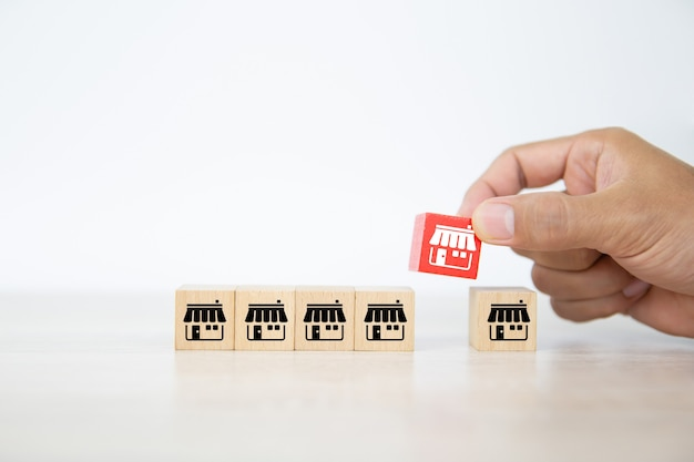 クローズアップの手はフランチャイズビジネスストアと積み重ねられた立方体の木のおもちゃのブロックを選択します。