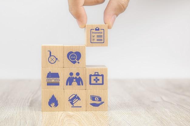 クローズアップ手は安全家族保険のための保険アイコンが付いている立方体の木のおもちゃのブロックを選択します
