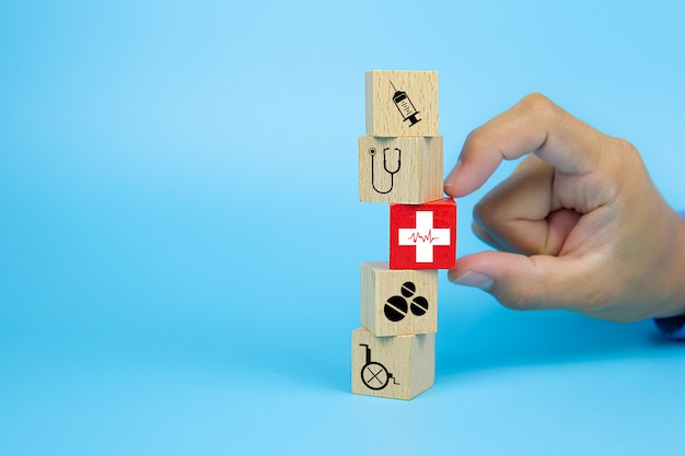 Close-up hand choose a cube wooden toy blocks with a red cross heart rhythm icon stacked for medical and health insurance concepts.