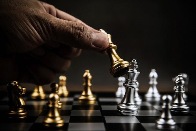 Close up hand choose gold chess to fight with silver chess team on chess board