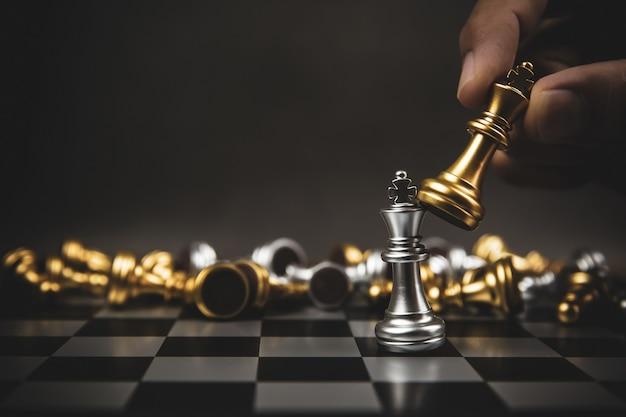 Крупным планом рука выбирает золотые шахматы, чтобы сражаться с серебряной шахматной командой на шахматной доске