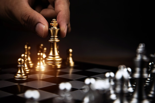 Close up hand choose king chess challenge with other chess team.