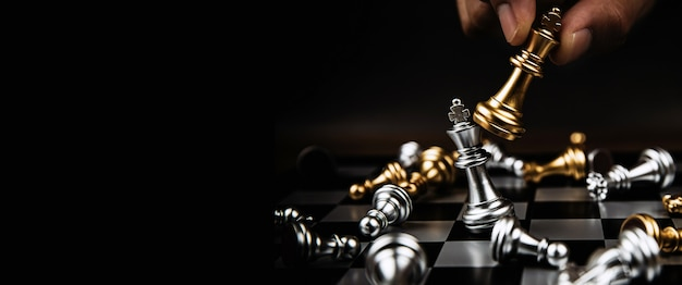 Close-up hand choose the king chess to fight with silver team