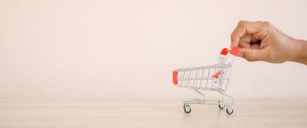 Close up hand choose mini shopping cart.