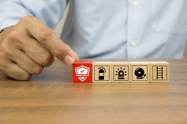 Close-up hand choose prevent icon on cube wooden toy blocks stacked with fire exit prevention icon.