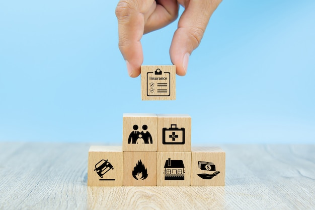 Close-up hand choose a red wooden toy blocks with insurance icon for safety family insurance
