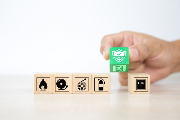 Close-up hand choose wooden blocks stacked with protect and door exit icon.
