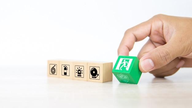 クローズアップの手は、ドア出口標識のある木製のブロックを選択します。