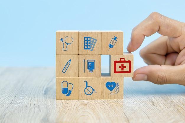 Рука конца-вверх выбирает деревянные блоки игрушки с значком сумки медицинского оборудования для концепций медицинской страховки.