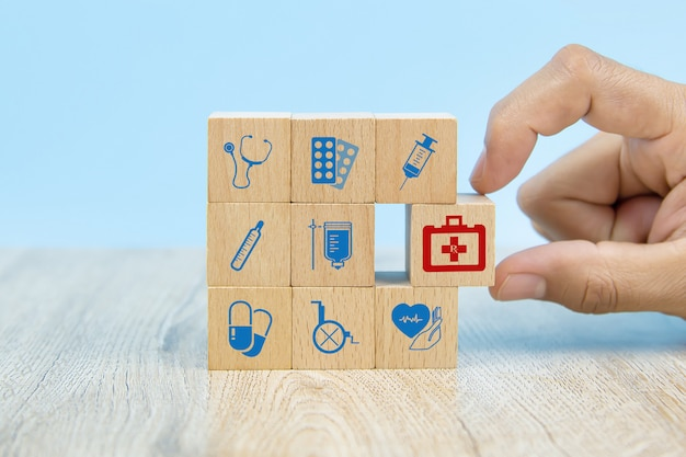 Close-up hand choose wooden toy blocks with medical equipment bag icon for health insurance concepts.
