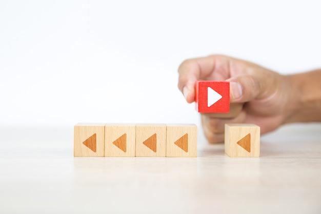 クローズアップの手は、積み重ねられた立方体の木のおもちゃのブロックの矢印アイコンを選択します