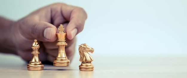 Close-up hand chooses king chess standing with a team.