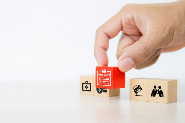 Close-up hand chooses red wooden blocks stacked with insurance icon.
