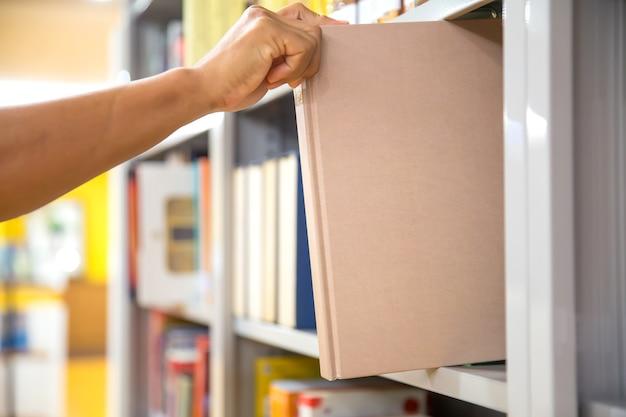 本棚から本を選んで手を閉じます。