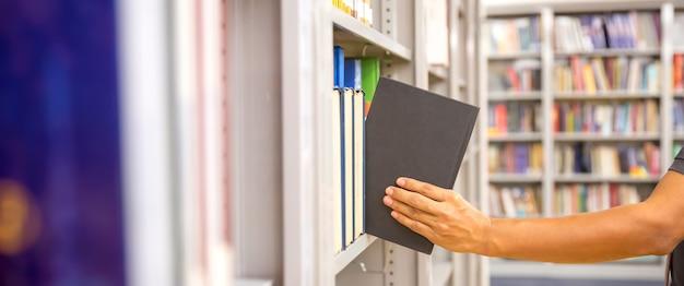 책장에서 책을 선택하는 손을 닫습니다.
