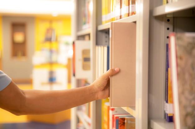 Закройте руку, выбирая книгу с полки.