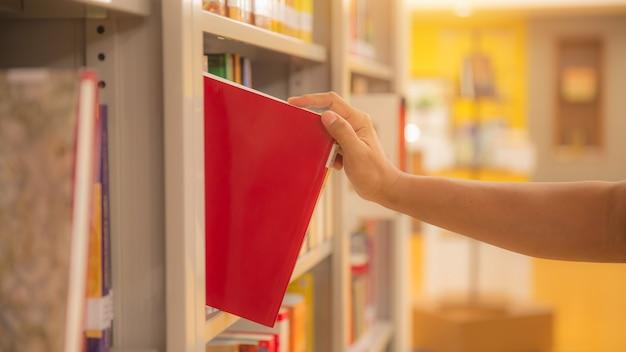 Close up hand choosing a book from bookshelf.