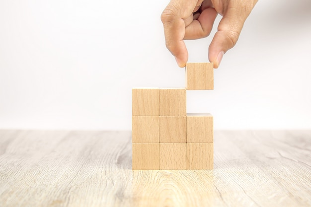 Close-up hand choosing cube wooden block toy stacked without graphics.