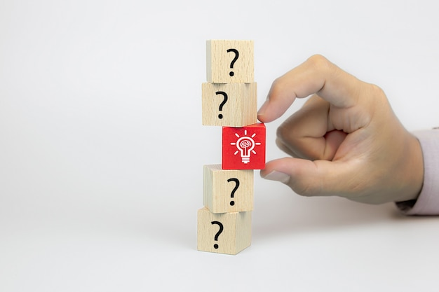 Close up hand choosing a light bulb icon from question mark symbol on cube wooden toy blocks