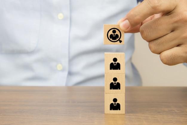 큐브 나무 장난감 블록 개념 비즈니스 조직 및 리더십에 대 한 인적 자원에 돋보기 아이콘에서 사람들을 선택하는 손을 닫습니다.