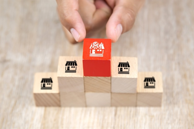 Close-up hand choosing wooden block stack with franchise icon.