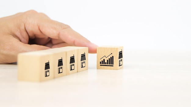 Close-up hand choosing wooden block stack with graph and franchise icon.