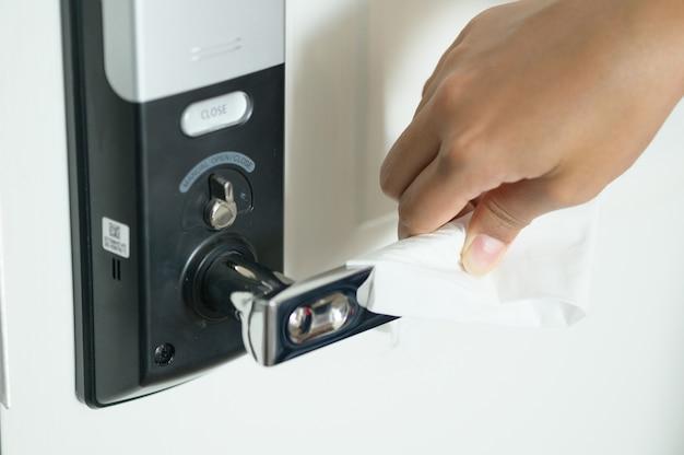 ウイルスに対してペーパーティッシュで消毒された金属製のドアハンドルのドアノブをクリーニングする手のクローズアップ