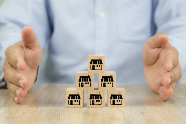 Close-up hand and cube wooden toy blocks stacked in pyramid with franchise business store icon.