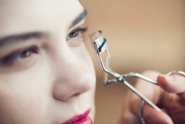 Close-up hand curling eyelashes of model