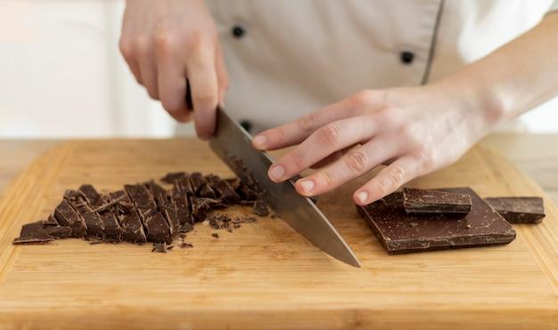 Chiuda sul cioccolato di taglio della mano