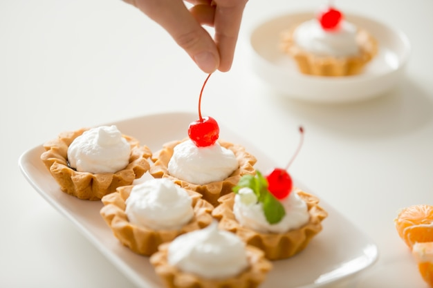 Close up of hand decorating mini cream tarts with cherry