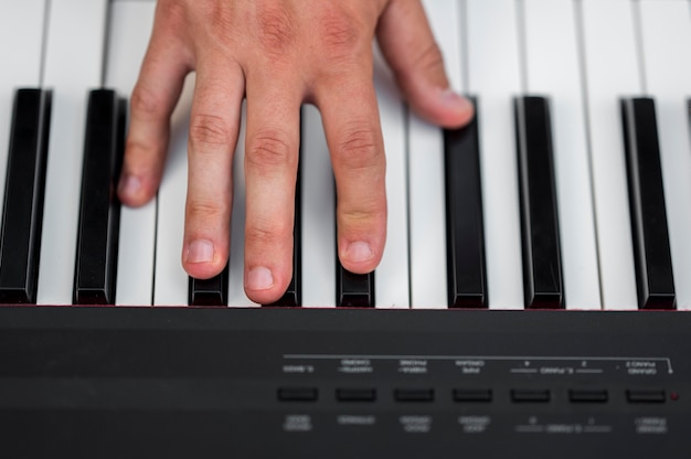 Mano del primo piano sulla vista superiore del piano digitale