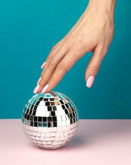 Close up hand and disco globe