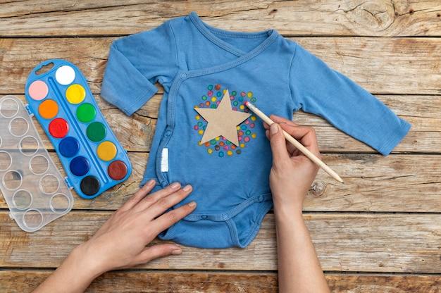 Mano del primo piano che attinge vestiti del bambino