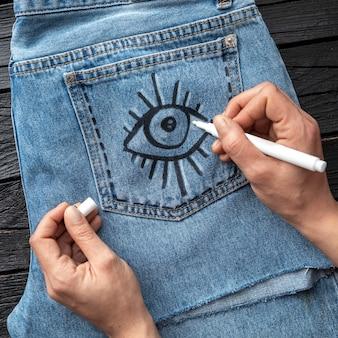 Mano del primo piano che attinge jeans