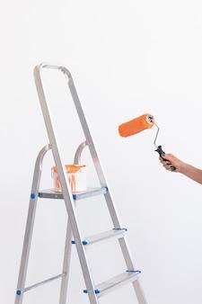 클로즈업 손 여성은 페인트 롤러로 벽을 페인팅합니다. 그녀의 새 아파트에서 젊은 아름 다운 여자 그림 벽의 초상화. 재장식 및 개조 개념입니다.