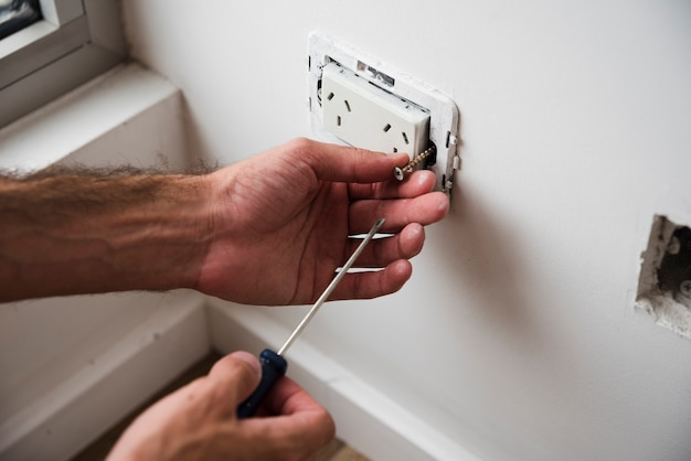 Close-up of hand fixing plug socket using screwdriver
