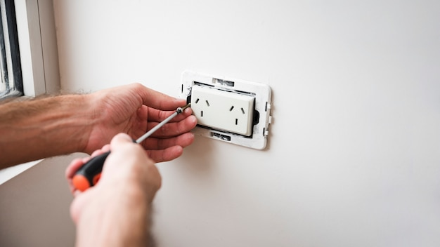 Close-up of hand fixing plug socket on white wall