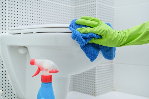Close-up of hand in gloves with rag and detergent washing hanging toilet