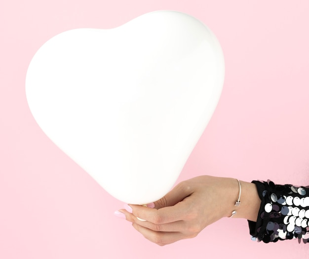 Close up hand and heart shaped balloon
