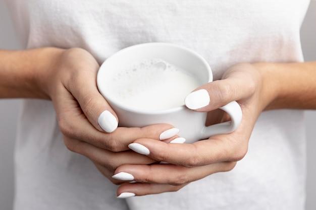 Close-up of hand held mug of milk