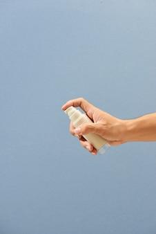 Крупным планом рука держит маленькую бутылку с распылителем и распыляет