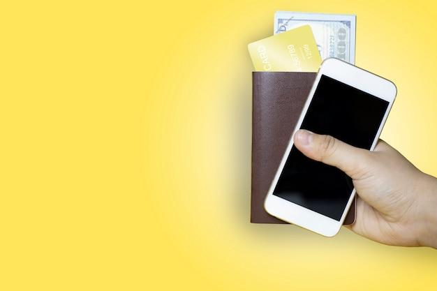 갈색 여권을 들고 있는 손과 달러 지폐와 금색 신용 카드가 들어 있는 휴대 전화, 노란색 배경, 국제 여행에 사용되는 여권, 클리핑 패스.