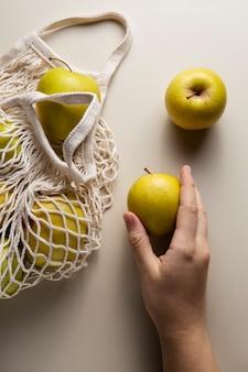Крупным планом рука держит яблоко